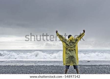 man in yellow rain coat standing in front of the ocean and raising his arms into the air