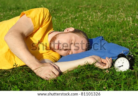man in yellow shirt sleeping on summer meadow near clock, lying on side, rest concept