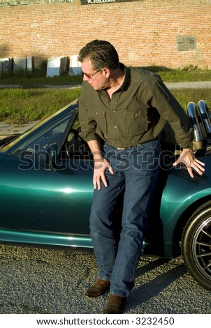 Man inclined slightly looking towards the front of his car as if concerned that his tire may be flat. - stock photo
