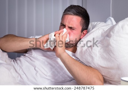 Man Infected With Cold And Flu Blowing His Nose In Tissue Paper - stock photo