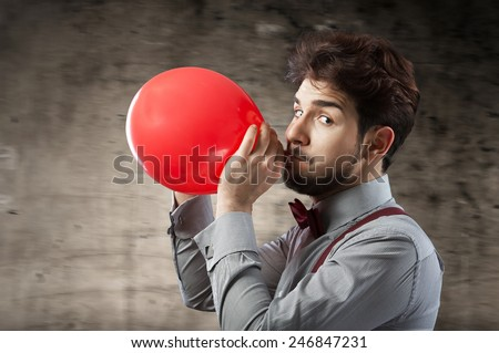 Man inflating a red balloon by mouth - stock photo