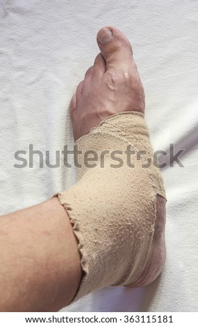 Man injured ankle and foot wrapped in bandage - stock photo