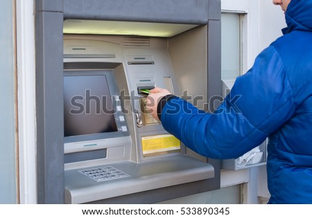 Man insert credit card in atm