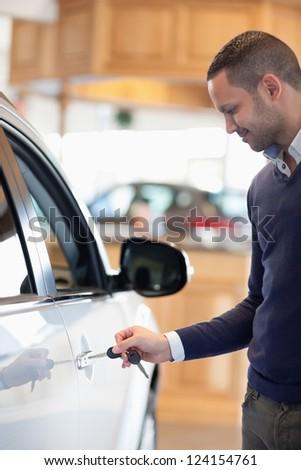 Man inserting a car key in a car - stock photo