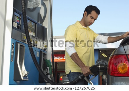 Man inserting nozzle in fuel cap of a car - stock photo