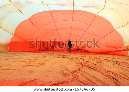 man inside a hot air orange color balloon background, transportation, A background with an abstract view of a colorful parachute - stock photo
