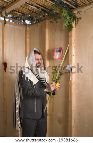 man inside a sukkah wearing prayer shawl holds lulav and etrog in the traditional manner for the jewish holiday of sukkoth - stock photo