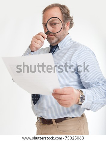 Man inspecting a document through a magnifying glass - stock photo