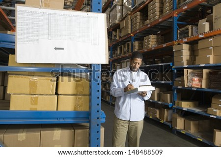 Man inspecting boxes in distribution warehouse - stock photo