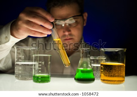 Man inspecting contents of test tube - stock photo