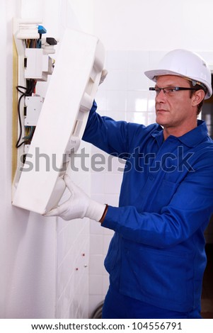 Man inspecting fuse box - stock photo