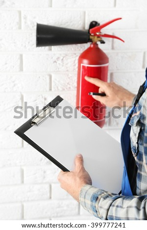 Man inspecting the fire extinguisher against white brick wall background - stock photo