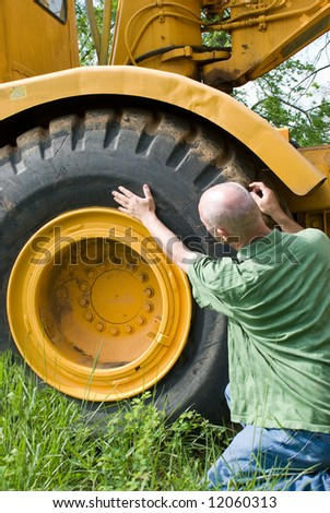 Man inspecting tire on earthmover - stock photo