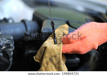 Man inspects the level of oil on a car engine dipstick - stock photo