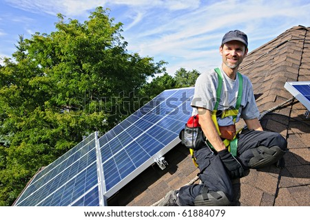 Man installing alternative energy photovoltaic solar panels on roof - stock photo