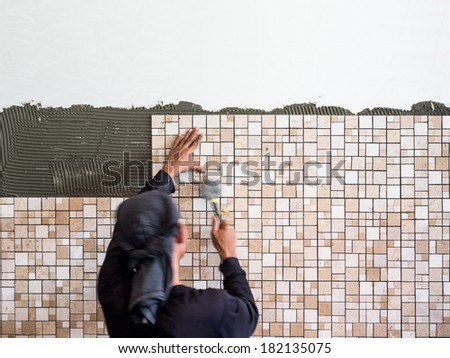 Man installing ceramic wall tile with a rubber hammer - stock photo