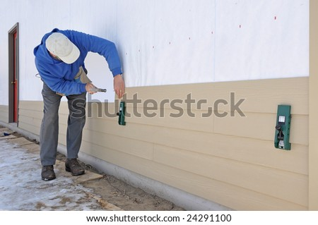 Man installing fibrous cement siding using siding gauges - stock photo