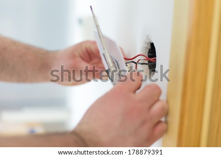 Man installing light switch after home renovation - stock photo