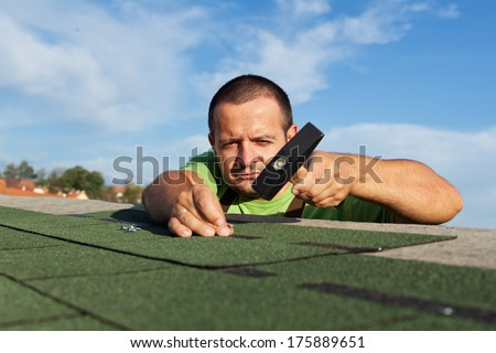 Man installing or repairing roof with bitumen shingles - fastening the pieces with nails - stock photo