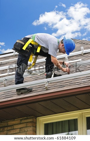 Man installing rails for solar panels on residential house roof - stock photo