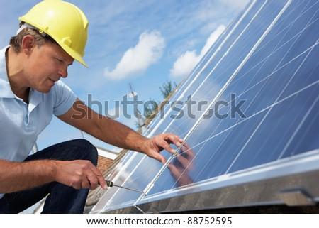 Man installing solar panels - stock photo