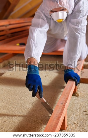 Man installing thermal insulation layer under the roof - using mineral wool panels, cutting to fit - stock photo