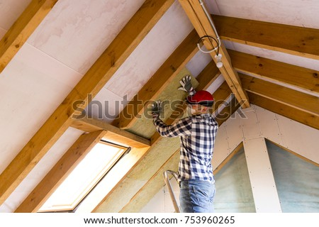 Man Installing Thermal Roof Insulation Layer   Using Mineral Wool Panels.  Attic Renovation And Insulation