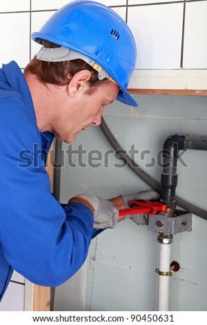 Man installing water pipes with a large wrench