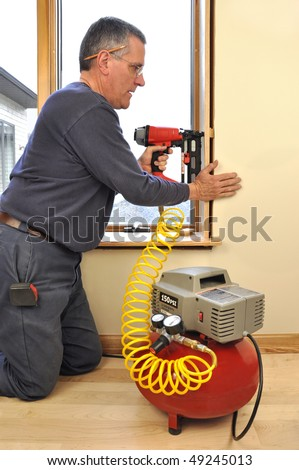 Man installing window jam extensions using nail gun powered by air compressor - stock photo