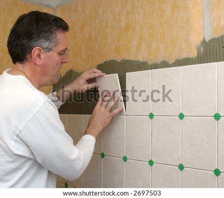 Man installs ceramic tile in bathroom shower - stock photo