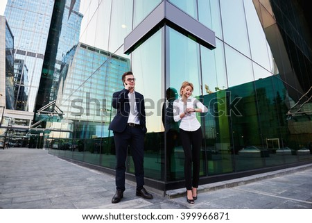 Man intelligent economist is phoning via cell telephone, while is standing with partner outside the company where they work. Blonde female is checking time, while her boss is talking on mobile phone - stock photo