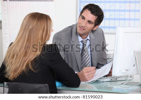 Man interviewing a young woman across a desk - stock photo