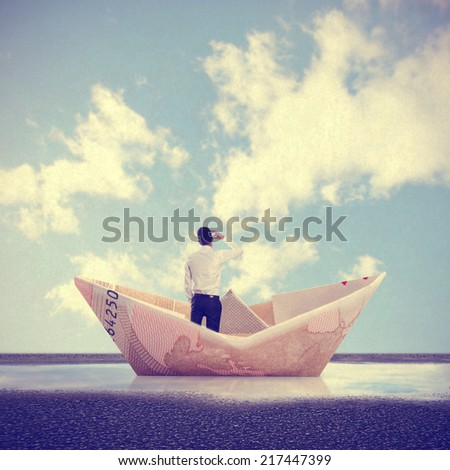 man into a bill boat on a puddle - stock photo