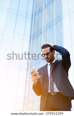 Man investor reading shocking news on mobile phone about falling shares on stock exchanges, male received a message on cell phone the fact that clients is tearing the agreement on further cooperation - stock photo