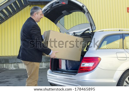 Man invites box in the trunk of the car - stock photo