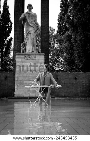 Man ironing his suit in a fountain the city - stock photo
