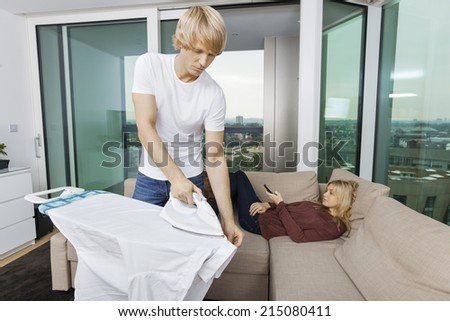 Man ironing shirt while woman relaxing on sofa at home - stock photo