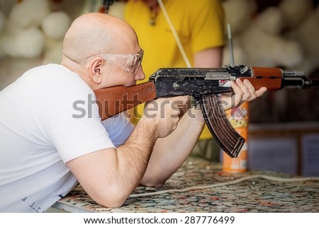 Man is aiming a gun in the shooting-range. Image with selective focus - stock photo