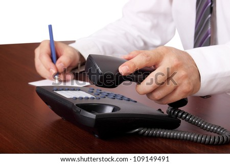 man is answering or hanging up the phone in an office - stock photo