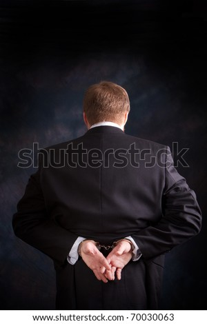 Man is arrested and handcuffed behind his back for white collar crime. - stock photo