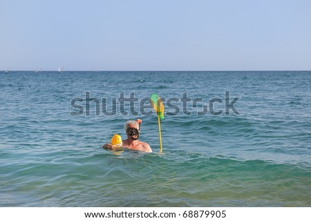 man is catching a toy fish in the sea while snorkeling - stock photo