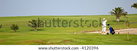 Man is checking the wind direction at exotic golf  course - stock photo