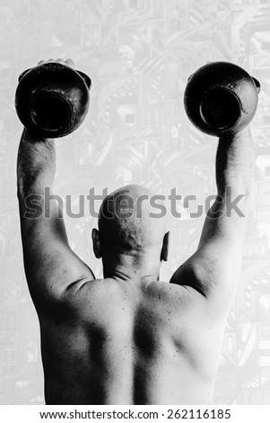 Man is doing exercises with two kettlebells. Black-and-white, vertical