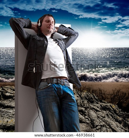 man is dreaming away while listen to good music on a beach - stock photo
