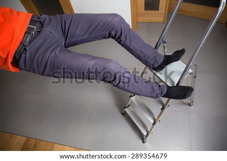 Man is falling down from ladder at home - stock photo