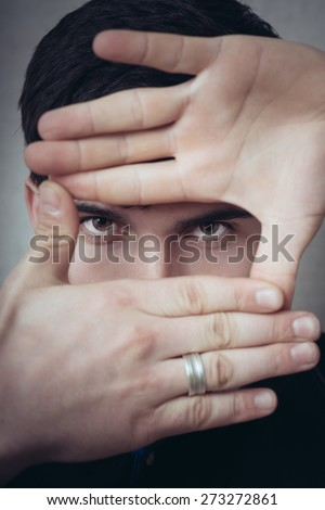 man is framing with his hands - stock photo