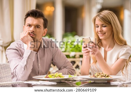 Man is getting bored in restaurant while his woman looking at phone. - stock photo