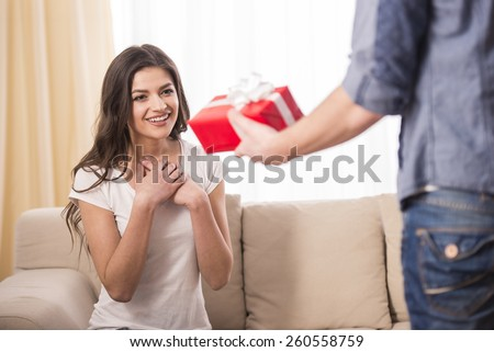 Man is giving a present to his girlfriend at home. - stock photo