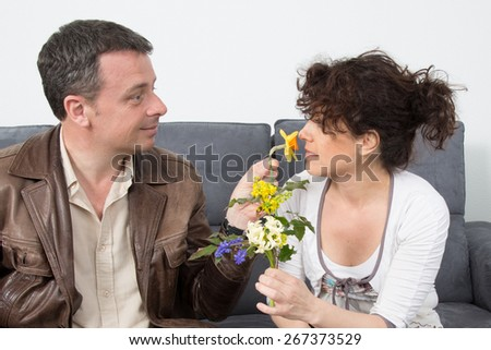 Man is giving flowers to his  girlfriend at home.