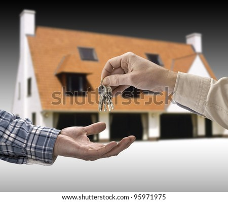 Man is handing a house key to a other man in the shape of the house. - stock photo